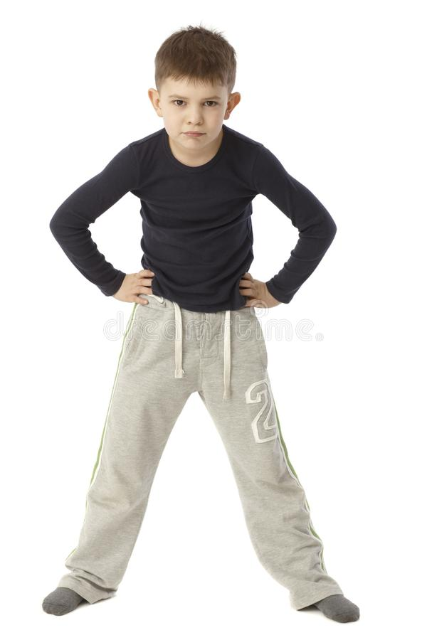 Little boy standing hand on hip looking strict. Little boy standing straddle with hands on hip, looking strict. Full size royalty free stock image