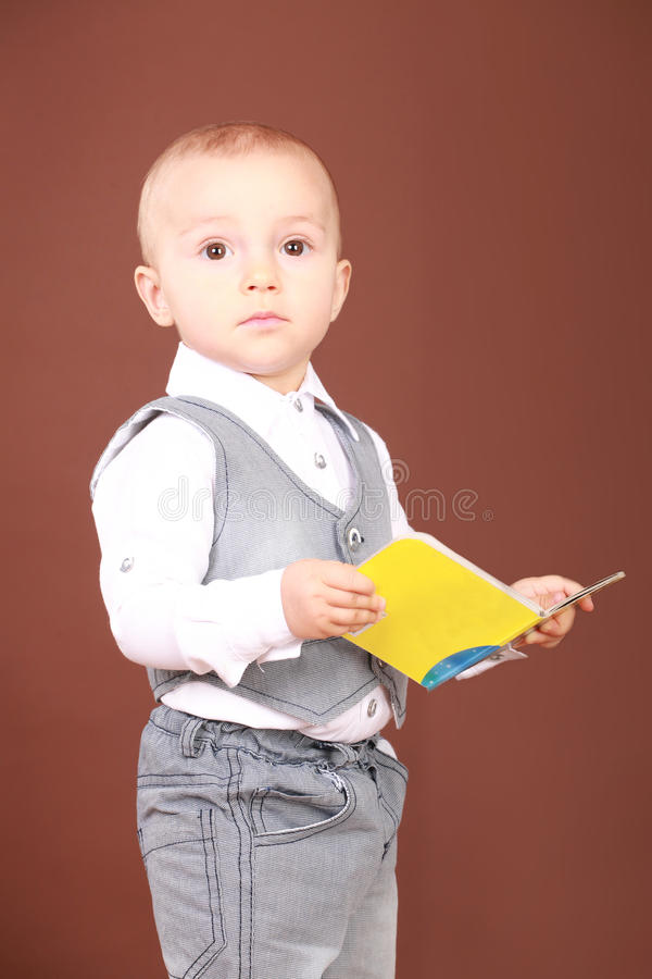 Little boy standing and holding a book in his hands stock image
