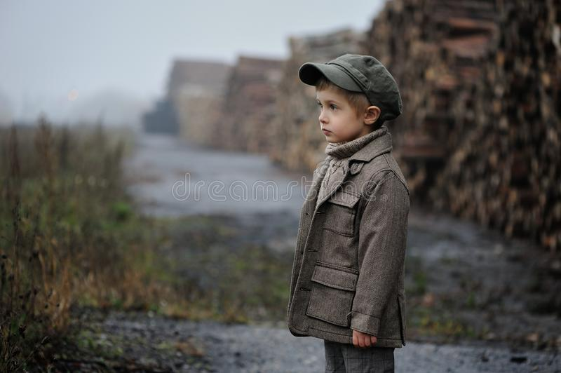 A little boy is standing and looking ahead in a foggy day. stock images