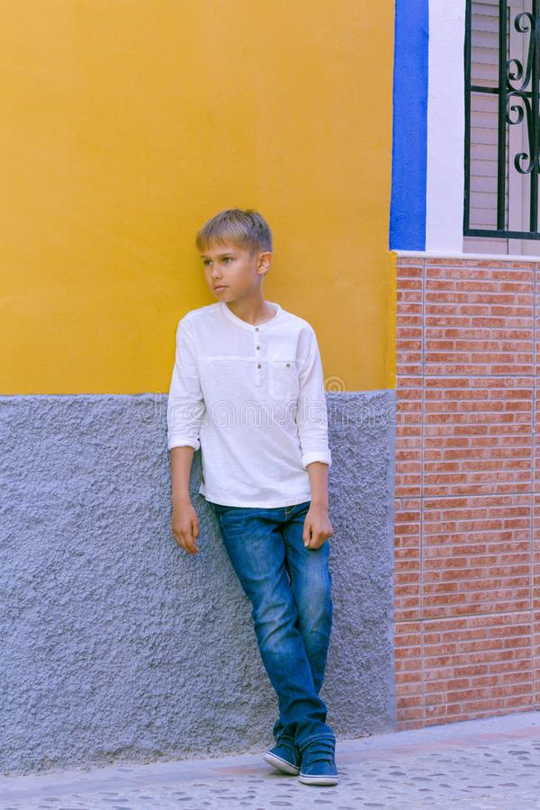 Little boy standing near coloful wall outdoors and looking away royalty free stock photos