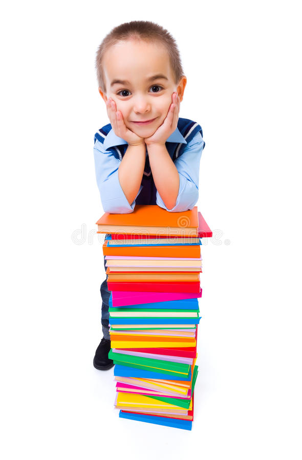 Little boy standing near stacked colorful books stock photography