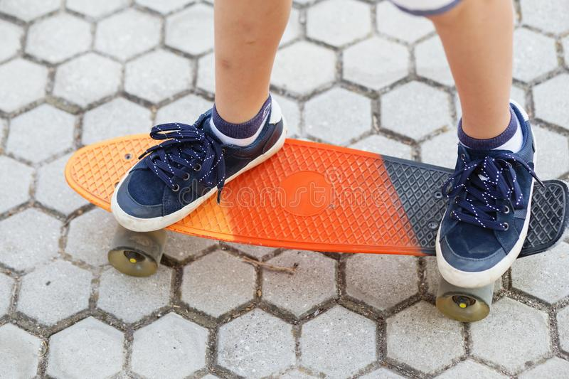 Little urban boy with a penny skateboard. Young kid riding in th stock photography
