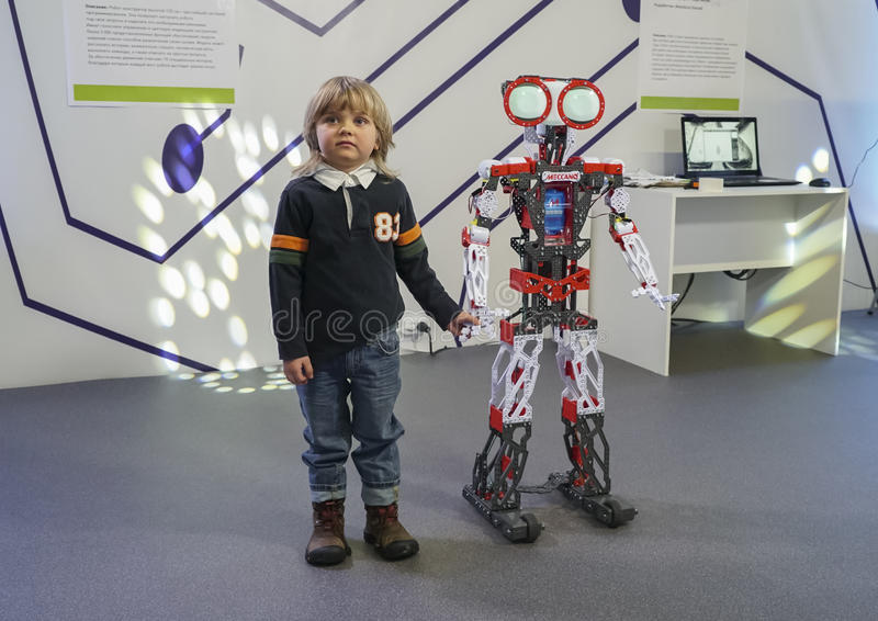 Little boy standing with the robot and holding hands stock photography