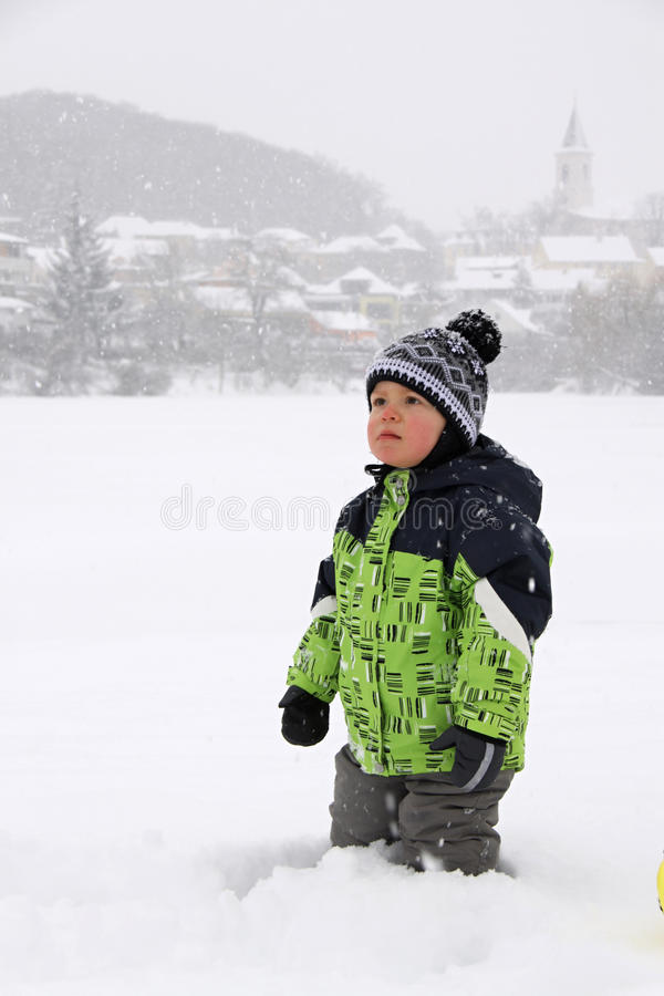 Little boy standing in the snow with stocking cap stock image