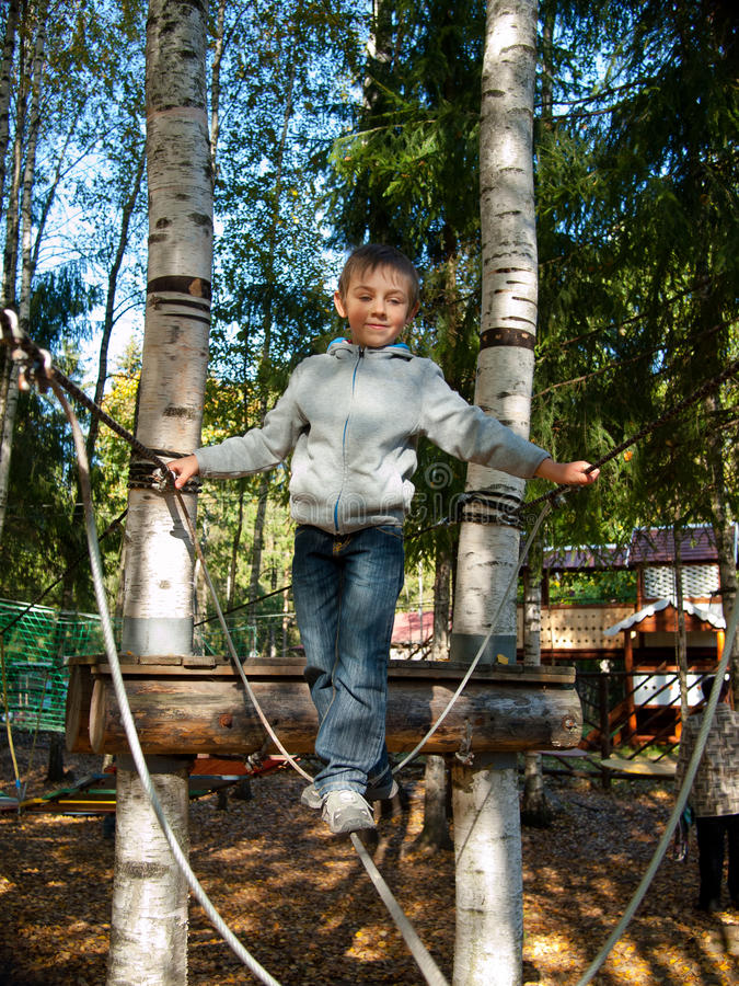 Little boy standing on a tightrope royalty free stock image