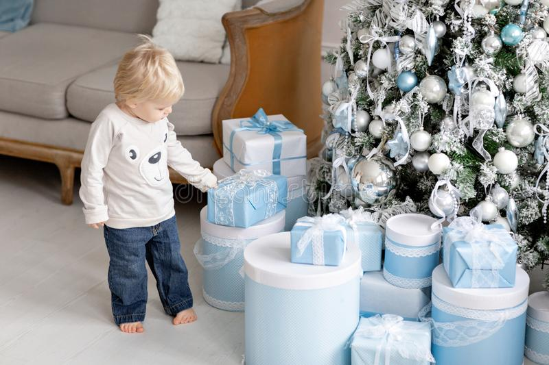 A little boy stands near a lot of gifts. Happy new year. decorated Christmas tree. Christmas morning in bright living. Portrait little boy. Happy new year stock images