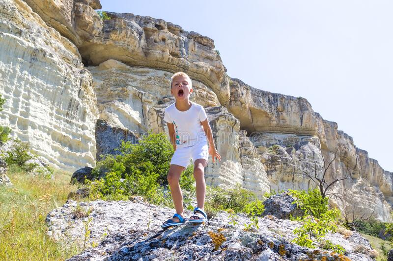 little boy stands on a rock in the mountains and growls like a dinosaur or a zombie stock photo