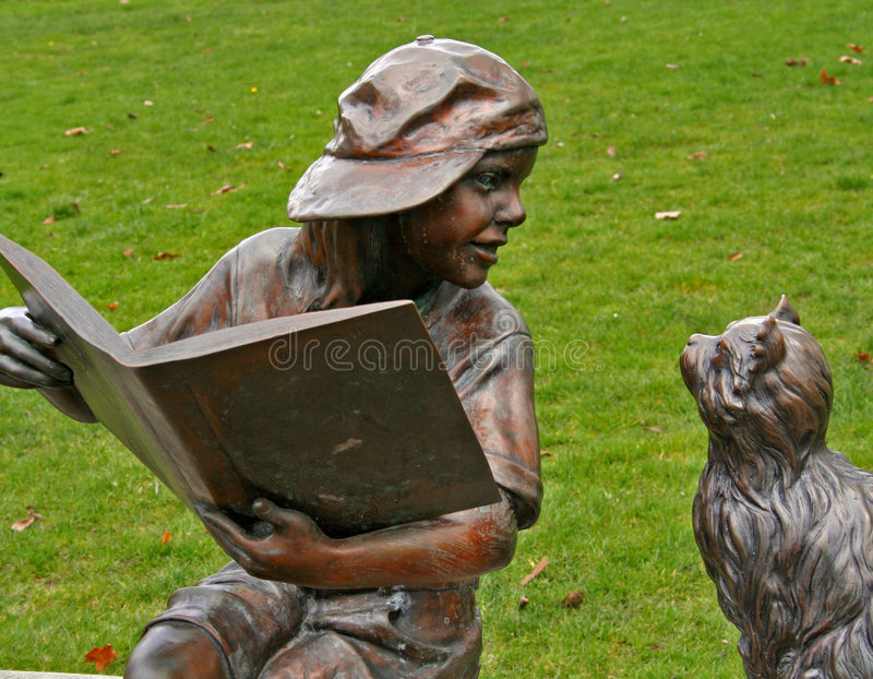 Little Boy Statue Reading to Cat stock image