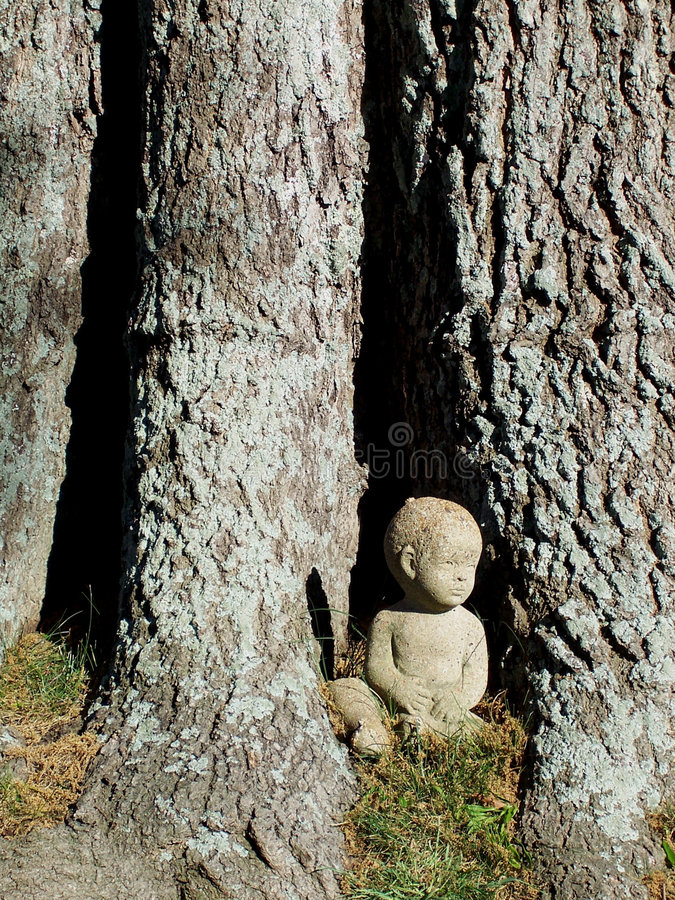 Little boy statue beside tree royalty free stock photo