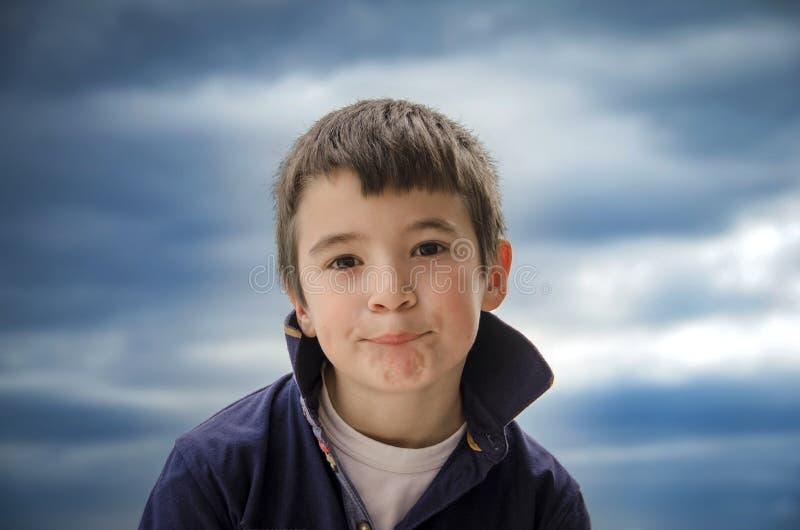 Little Boy stoi przed kamerą i robi śmiesznemu f obrazy royalty free