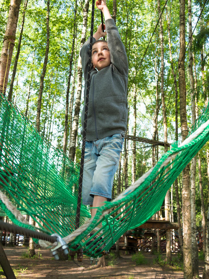 Little boy with a strained face goes on a rope. On the background of the forest stock photography