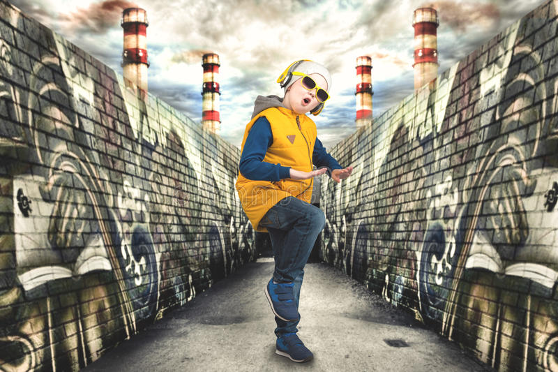 The little boy in the style of Hip-Hop . Children`s fashion.Cap and jacket. A Small Rapper.Graffiti on the walls.Cool rap DJ. stock image