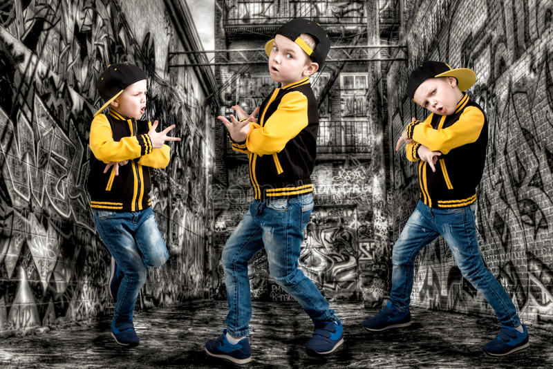 The little boy in the style of Hip-Hop . Children`s fashion.Cap and jacket. The Young Rapper.Graffiti on the walls.Cool rap dj. stock images