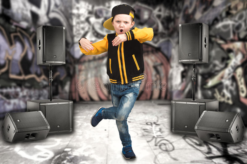 The little boy in the style of Hip-Hop . Children`s fashion.Cap and jacket. The Young Rapper.Graffiti on the walls.Cool rap dj. royalty free stock image