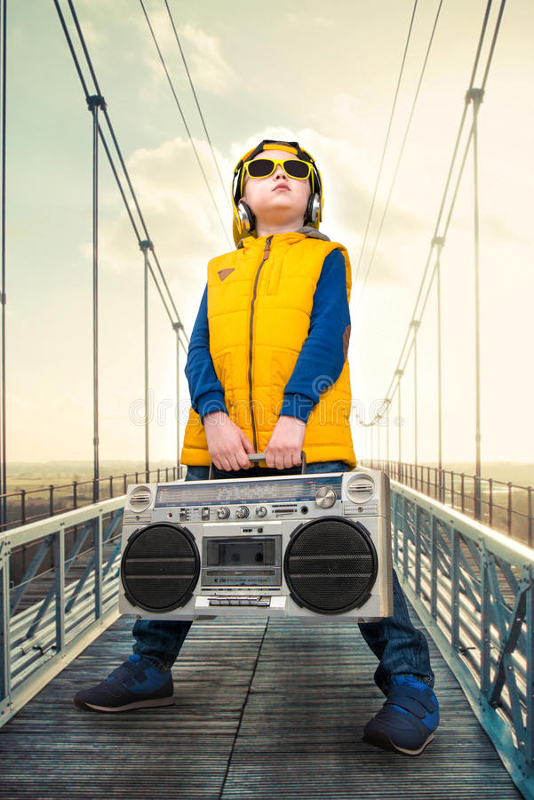 The little boy in the style of Hip-Hop holds a vintage tape recorder. The Young Rapper.Cool rap dj.Vintage Silver Radio boom box. stock images