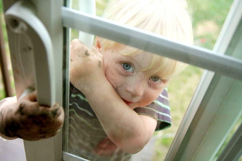 Little Boy sucio que mira a escondidas en ventana imagenes de archivo