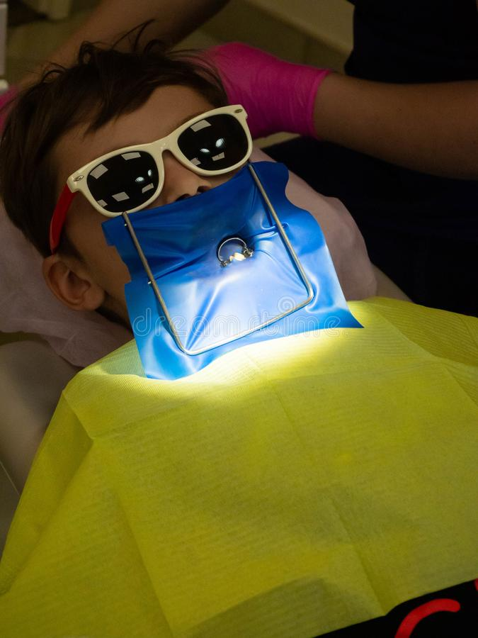 A little boy in dentistry office, Child treated teeth in the dental clinic. A little boy in sunglass in dentistry office, Child treated teeth in the dental royalty free stock images