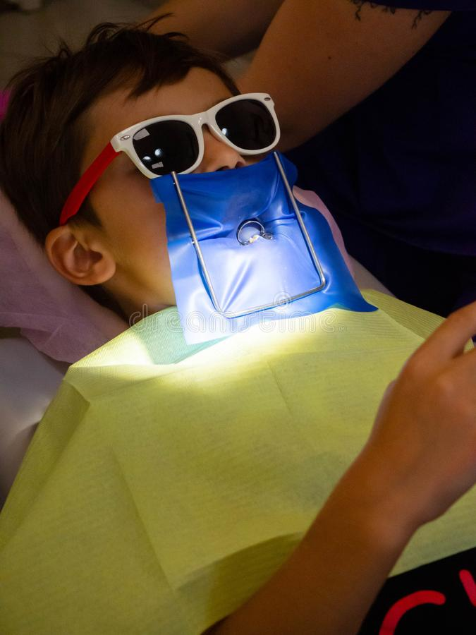 A little boy in dentistry office, Child treated teeth in the dental clinic. A little boy in sunglass in dentistry office, Child treated teeth in the dental stock photo