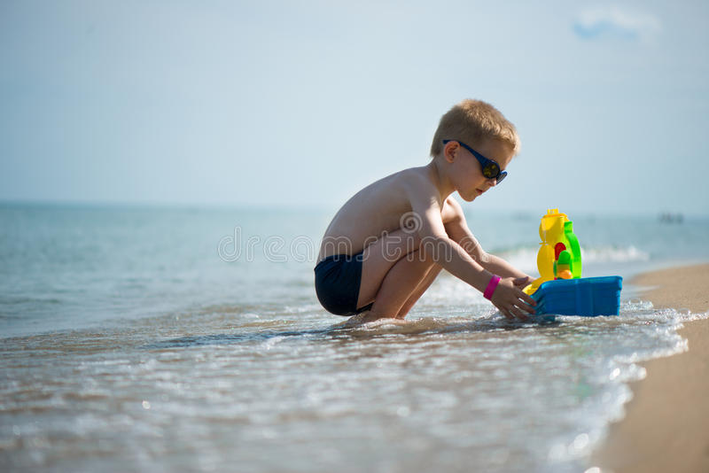 Little boy in sunglasses playing with toy boat stock photography