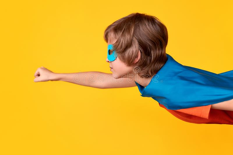 Little superhero flying to save world. Little boy in superhero costume clenching fist and flying against bright yellow background royalty free stock photos