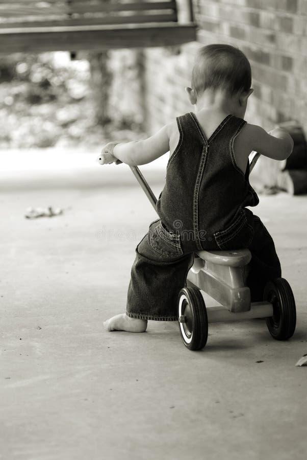 Little Boy sur le scooter dans la sépia photo stock
