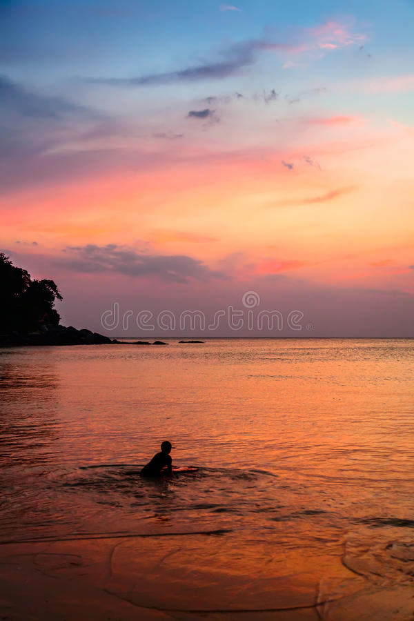 Little boy with surfboard at sunset royalty free stock photo