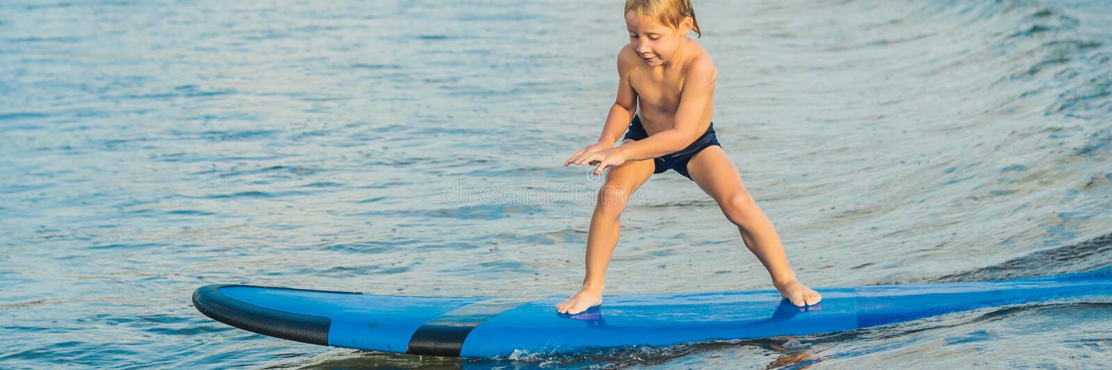 Little boy surfing on tropical beach. Child on surf board on ocean wave. Active water sports for kids. Kid swimming with. Surf. Surfing lesson for kids. BANNER royalty free stock photos