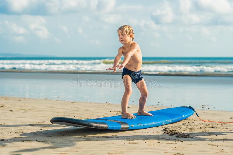 Little boy surfing on tropical beach. Child on surf board on ocean wave. Active water sports for kids. Kid swimming with. Surf. Surfing lesson for kids royalty free stock images