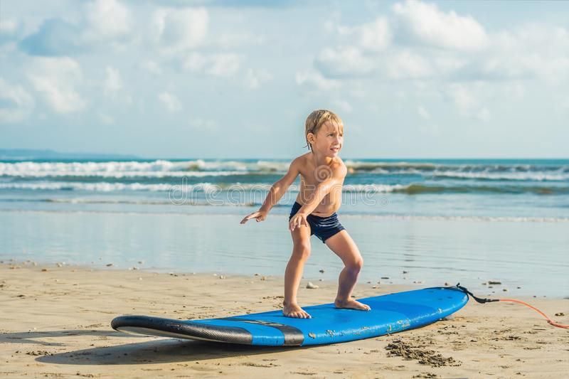 Little boy surfing on tropical beach. Child on surf board on ocean wave. Active water sports for kids. Kid swimming with royalty free stock image