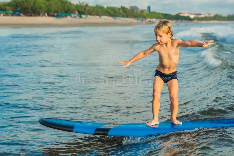Little boy surfing on tropical beach. Child on surf board on ocean wave. Active water sports for kids. Kid swimming with royalty free stock images