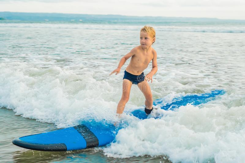 Little boy surfing on tropical beach. Child on surf board on ocean wave. Active water sports for kids. Kid swimming with stock images