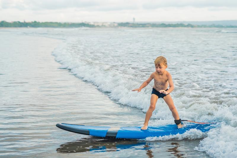 Little boy surfing on tropical beach. Child on surf board on ocean wave. Active water sports for kids. Kid swimming with royalty free stock photo