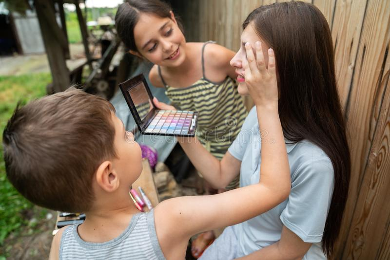 Little boy surprised with the makeup result, touching his sisters face with hand, children spending time together stock photo