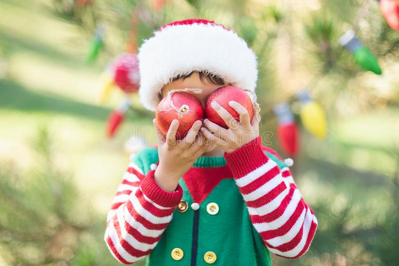 Little boy in sweater and hat waiting for a Christmas in the wood. Half-length portrait of a little boy near the christmas tree jumper child outside happy cold stock photo