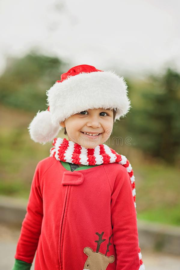 Little boy in sweater and hat waiting for a Christmas in the wood. Half-length portrait of a little boy near the christmas tree jumper child outside happy cold royalty free stock image