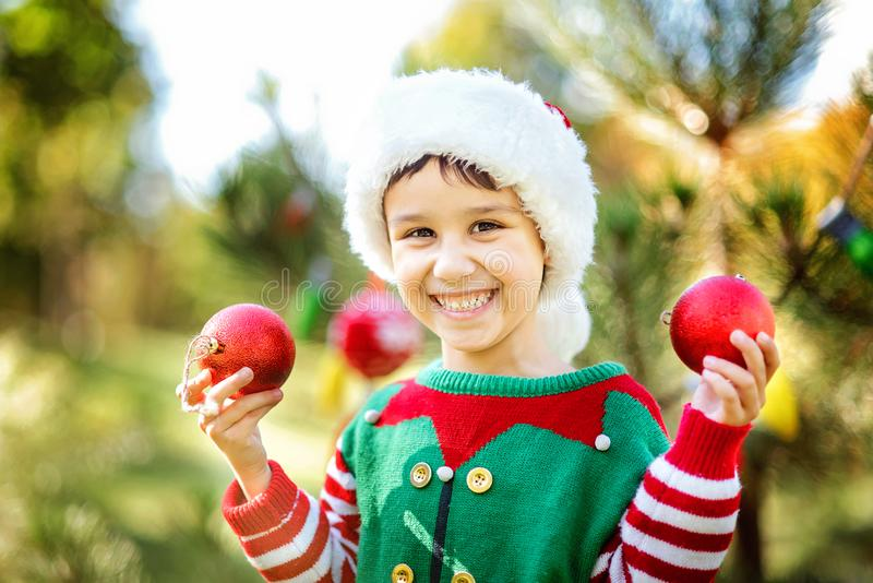 Little boy in sweater and hat waiting for a Christmas in the wood. Half-length portrait of a little boy near the christmas tree. Cute child decorating the royalty free stock image