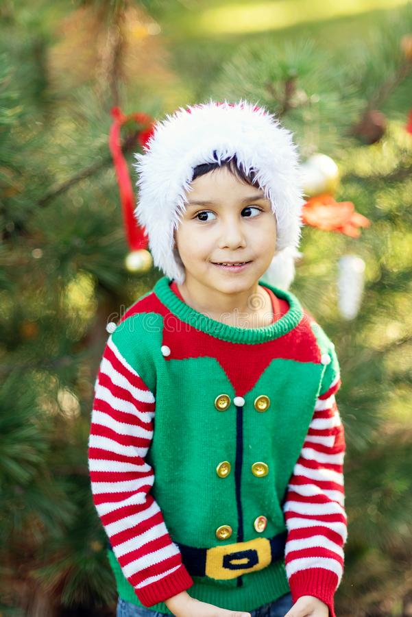 Little boy in sweater and hat waiting for a Christmas in the wood. Little boy near the christmas tree. Cute child decorating the Christmas tree outdoor. Merry royalty free stock photos
