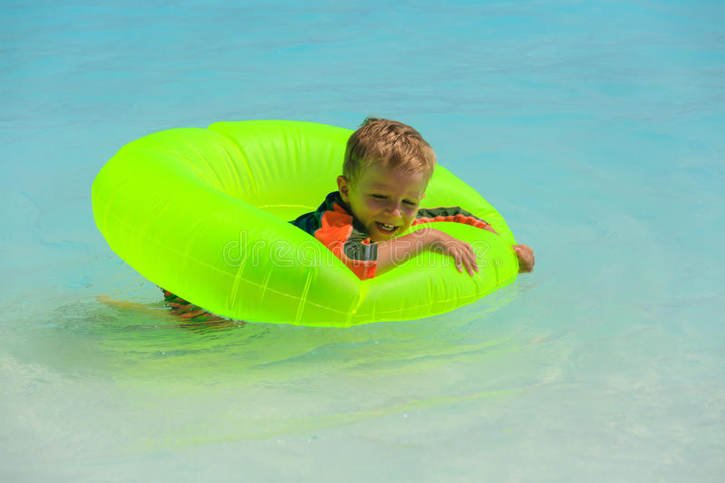 Little boy swimming at the beach. Little boy swimming at tropical beach royalty free stock images