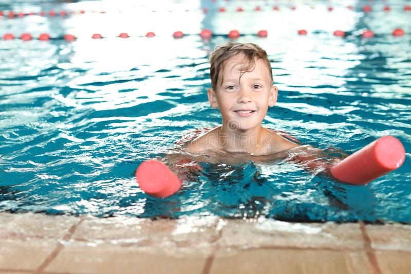 Little boy with swimming noodle in pool stock photography