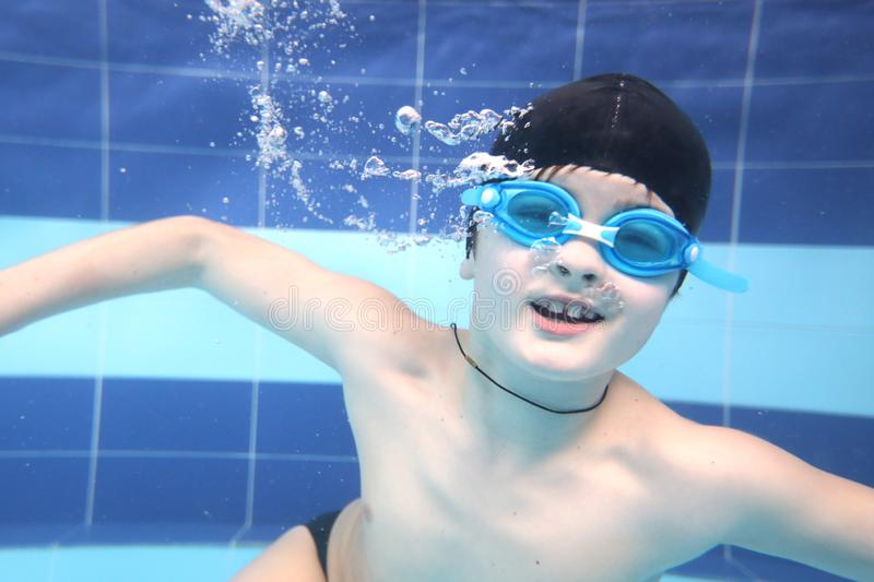 Little boy swimming  in pool  underwater royalty free stock photos