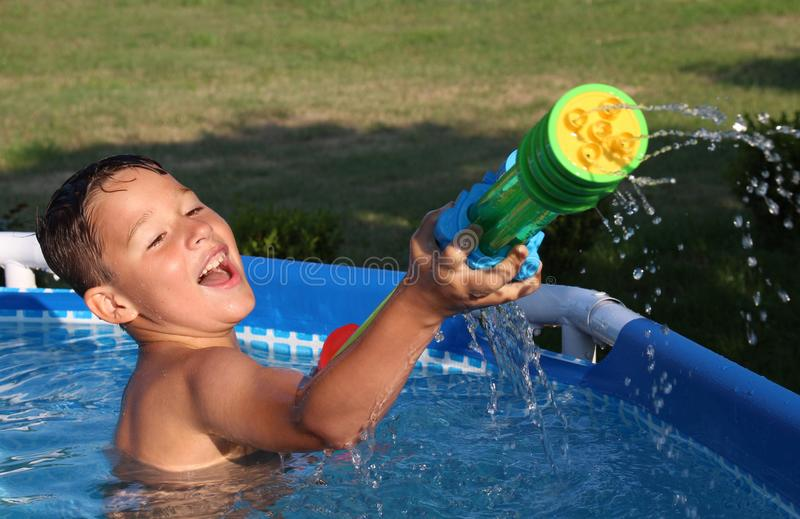 Little boy in the pool with water syringe stock photos