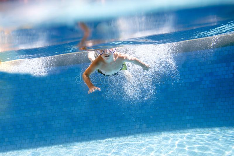 Little boy swims underwater swimming pool royalty free stock photos