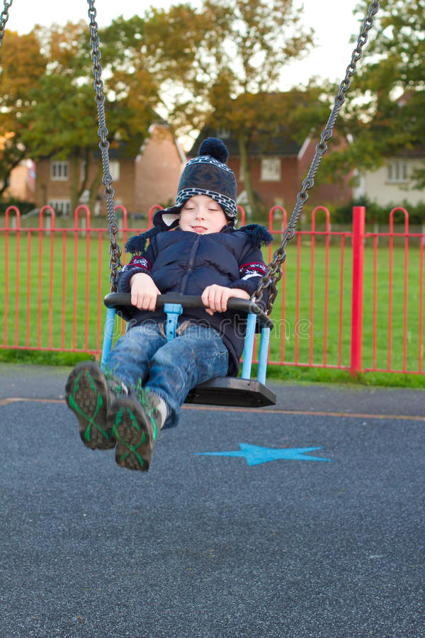 Little boy on a swing at the park royalty free stock images