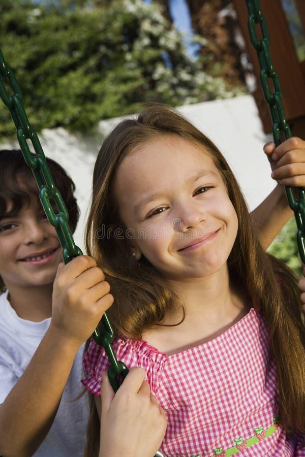 Little Boy Swinging Girl Stock Image