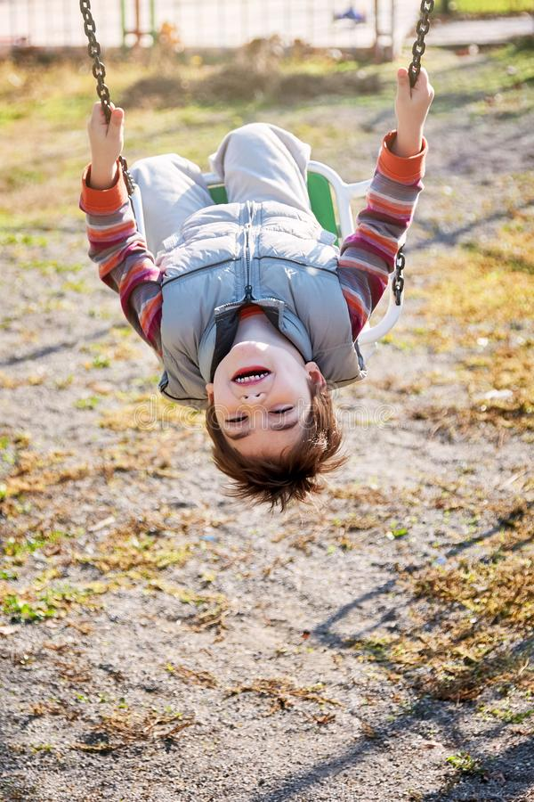 Little boy swinging and having fun on the chain swing stock image