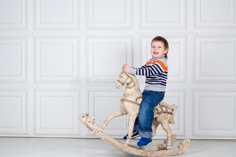 Little boy swinging on wooden horse. funny three-year-old boy in jeans and sweater on white background. Carefree childhood royalty free stock images