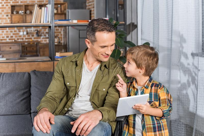 little boy with tablet in hand pointing at father stock images