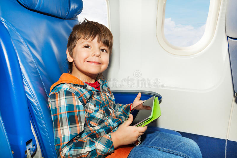 Little boy with tablet pc in airplane chair. Little boy sit with tablet computer in the airplane flying commercial liner royalty free stock image