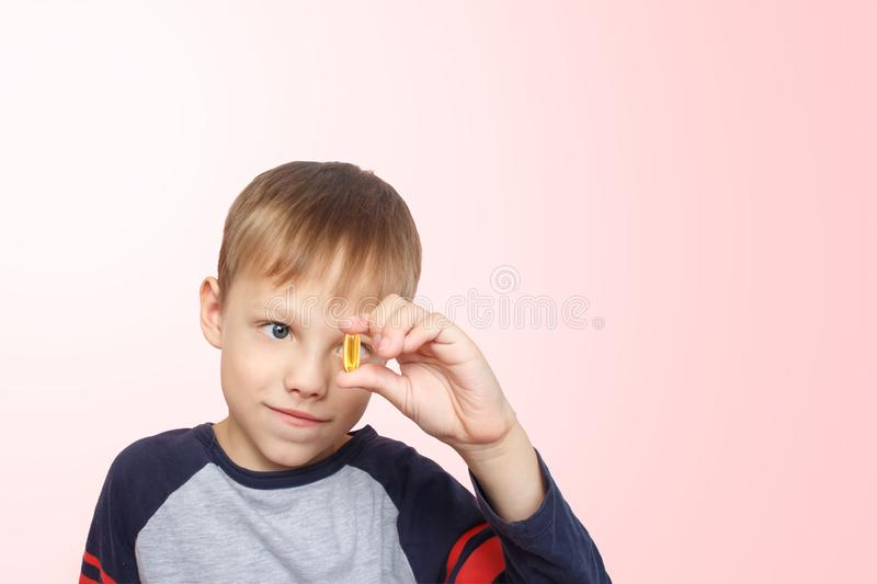 Little boy takes fish oil. Vitamins D, E. The child holding omega-3 capsule between his fingers. Healthy nutrition. Copy spase royalty free stock photos