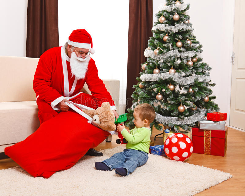 Little boy taking out toys from Santa's bag royalty free stock photography